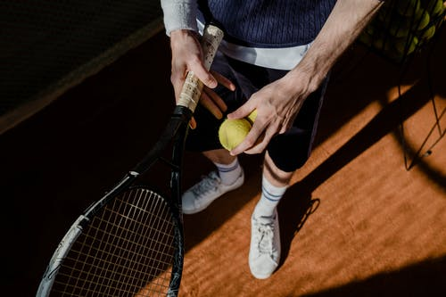 Person Holding Black and Yellow Tennis Racket