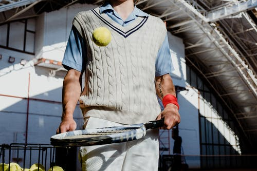 Man in White and Black Stripe Polo Shirt Holding Tennis Racket