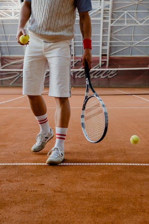 Man in White Shorts Holding Tennis Racket