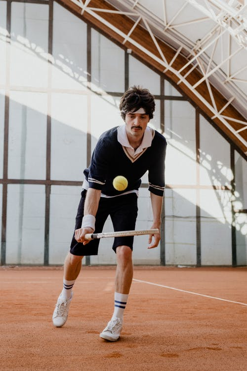 Man in Blue Polo Shirt and Black Shorts Holding Yellow Ball