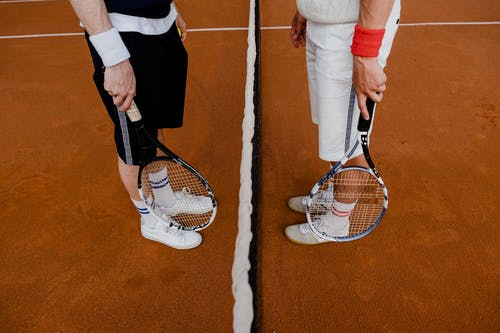Person in White Pants and Black Socks Standing Beside White and Black Tennis Racket