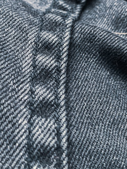 Closeup of textured dark denim fabric with straight stitch pattern with black thread on coarse jeans with frayed design on background
