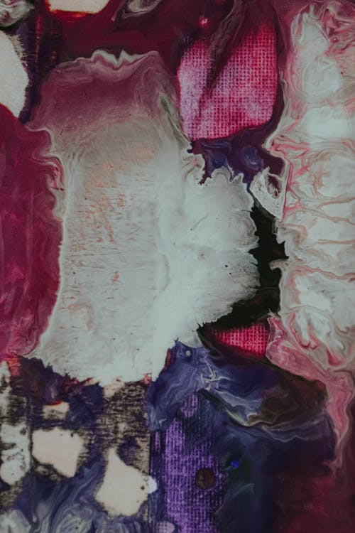 Overhead view of abstract backdrop of mixed acrylic paints with wavy stains on canvas