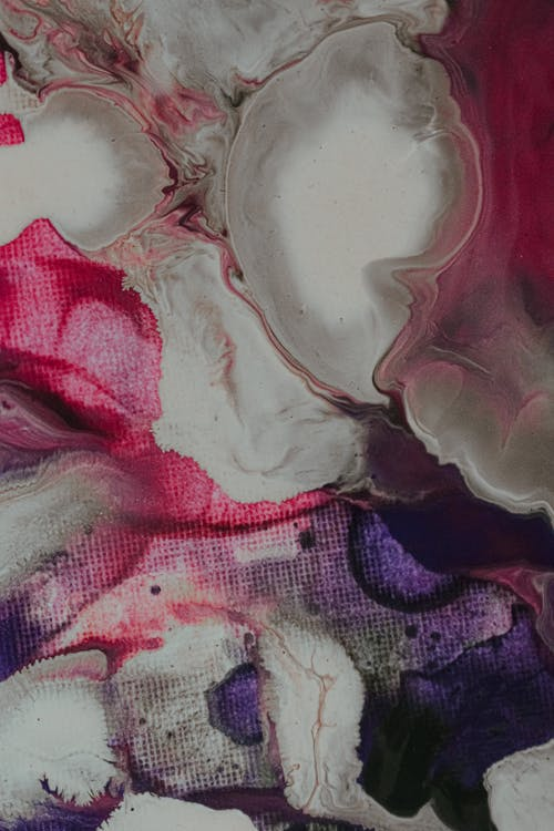 Overhead view of abstract backdrop of mixed watercolor paints with big blots and wavy lines