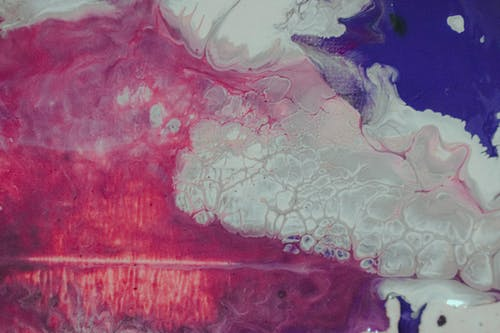 Top view of abstract backdrop representing bright blended acrylic paints with waves and stains