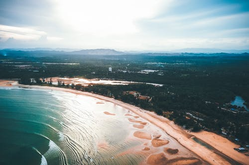 Drone view of wide sandy coast of wavy ocean surrounded by lush tropical green forests against cloudy blue sky