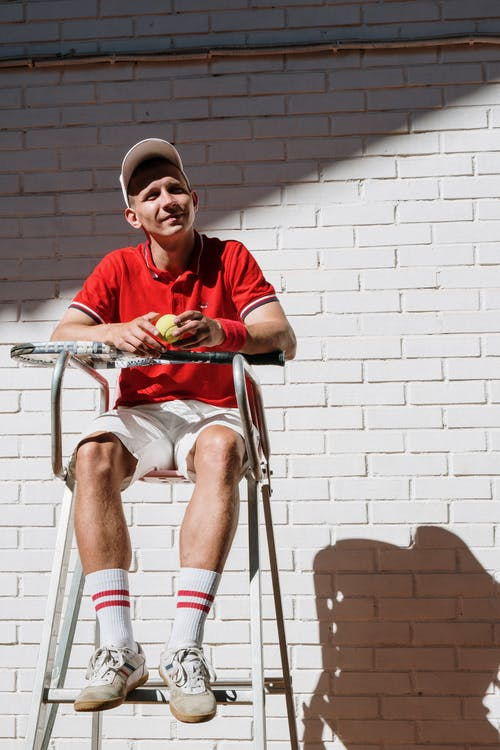 Man in Red and White Stripe Polo Shirt Sitting on Chair