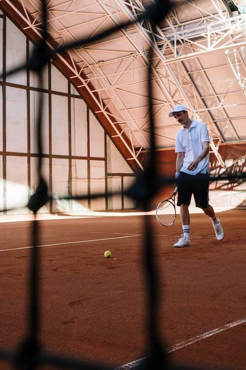 Man in White Shirt and Black Shorts Playing Tennis