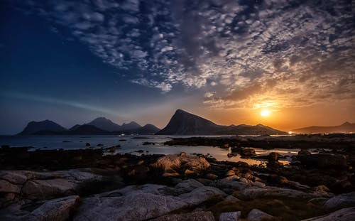 Picturesque Lofoten archipelago with rocky mountains and calm sea against cloudy sundown sky in Norway
