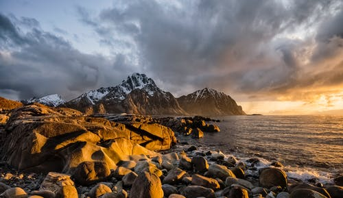 Rocky shore of picturesque sea against sundown sky