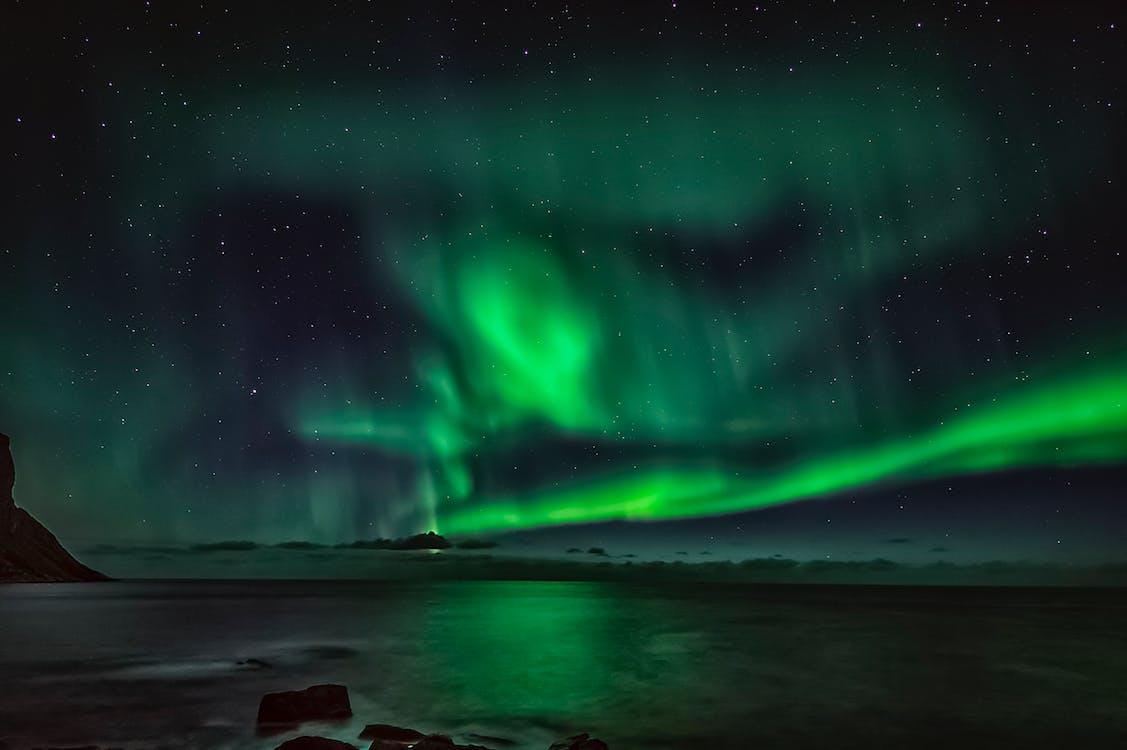 Starry night sky with green polar lights over waving ocean in mountainous terrain in winter