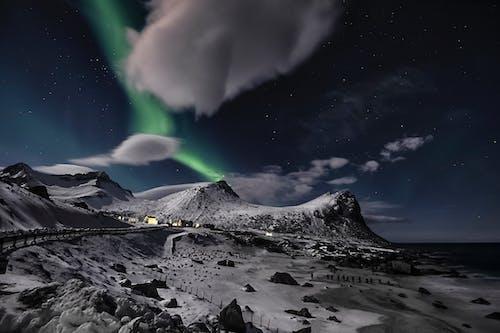 Aurora Boreale Nella Notte Stellata Sopra Le Montagne Innevate In Riva Al Mare