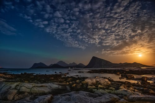 Magnificent landscape of sea waving on rocky coast near mountains in Lofoten archipelago against sunset sky