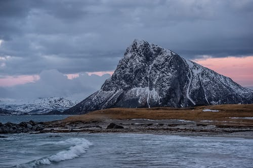 Mountain ridge and waving sea under cloudy sundown sky