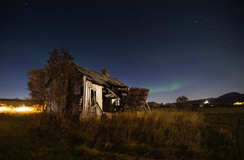Old ruined hut located on grassy field in countryside against night starry sky with northern light in Norway