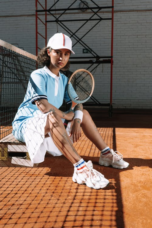 Man in White and Blue Robe Sitting on Tennis Racket