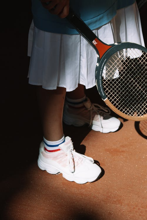 Person in White Nike Sneakers Standing Beside Orange and Black Electric Fly Swatter