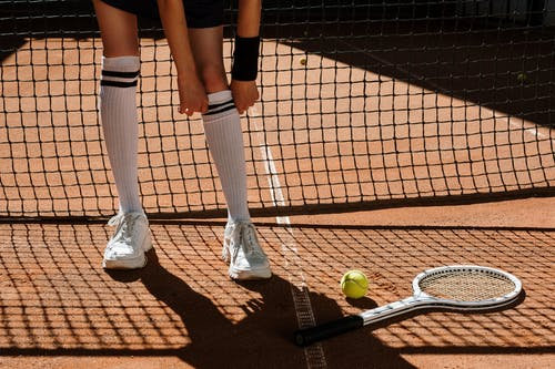 Person in Black Shorts and Black Socks Standing on Brown and White Tennis Court