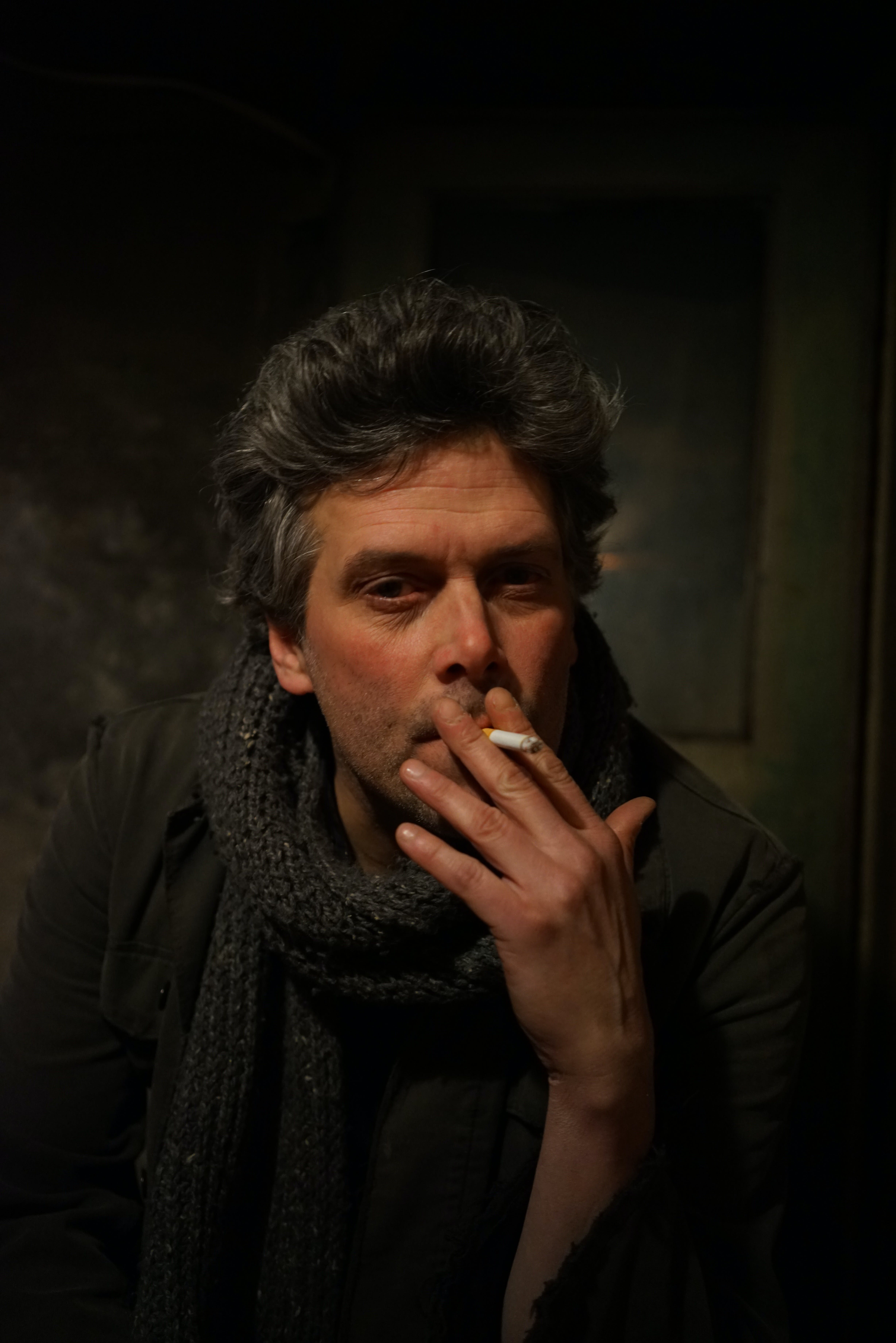 Man in Black Jacket With Gray Knit Scarf Smoking