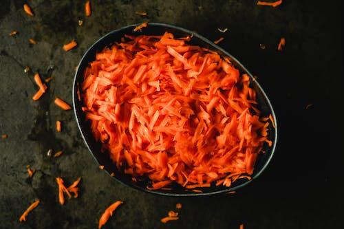 Heap of orange fresh grated carrot in baking pan