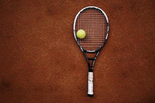 노란색과 검은 색 테니스 라켓