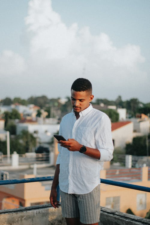 Young black man messaging on smartphone on terrace