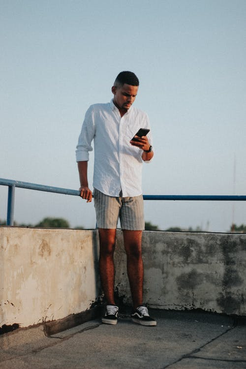 Focused young black guy surfing mobile phone on rooftop