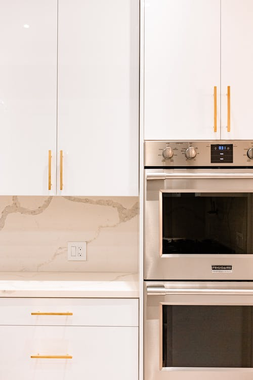 Kitchen interior with white cupboards and ovens