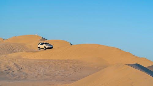 SUV car driving on sandy dunes in desert