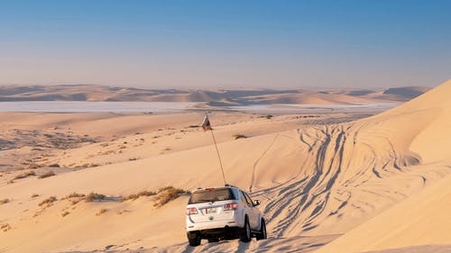 Off road car with flag driving on endless sandy terrain towards mirage and range of dunes