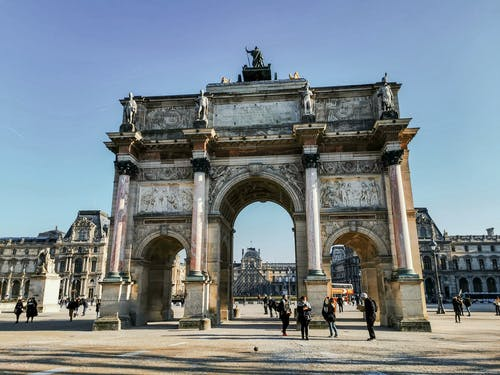 Old triumphal arch with sculptures on square with unrecognizable tourists