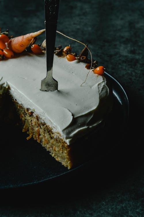 블랙 세라믹 접시에 스테인리스 포크로 케이크를 슬라이스