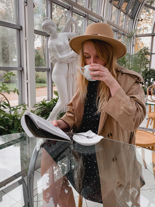 Young stylish woman drinking coffee and reading book in cafe