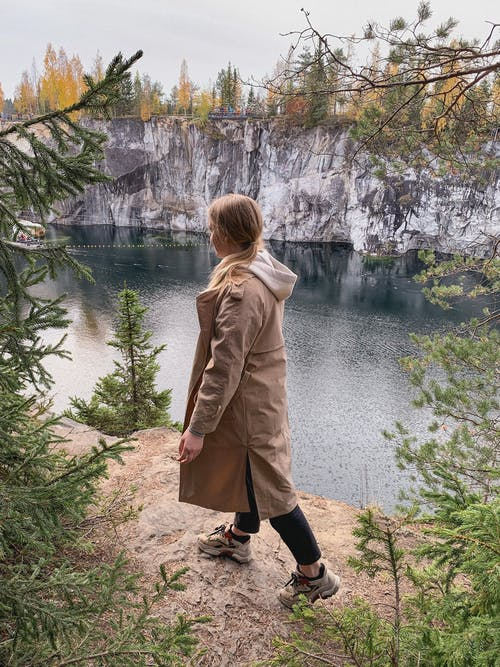 Side view of unrecognizable young female traveler in stylish outfit walking on rocky hill with growing trees and admiring rippling lake against cloudy sky