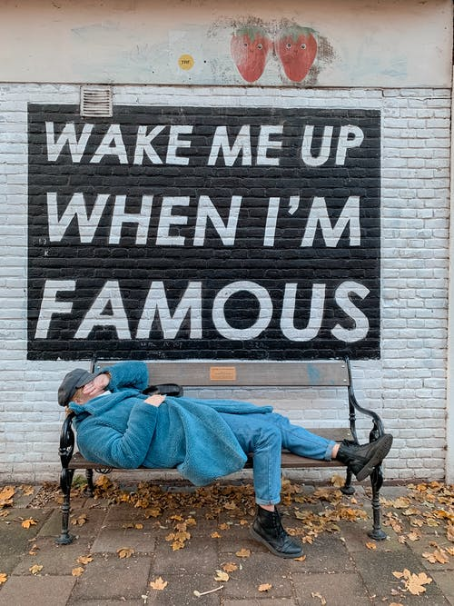 Side view of anonymous lady in fashionable coat and jeans covering face with hand while lying on bench placed on street near Wake Me Up When I M Famous inscription