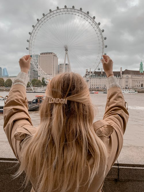 Anonymous female tourist relaxing on embankment and admiring London Eye observation wheel