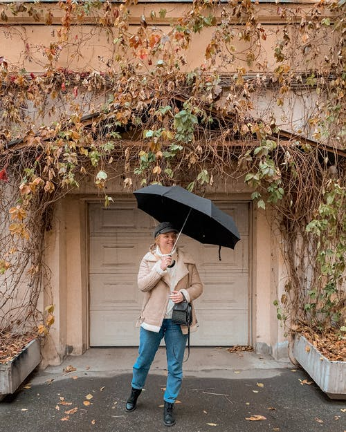 Full length of positive young female tourist in stylish outerwear and hat standing near residential building covered with autumn tree branches with umbrella and looking away