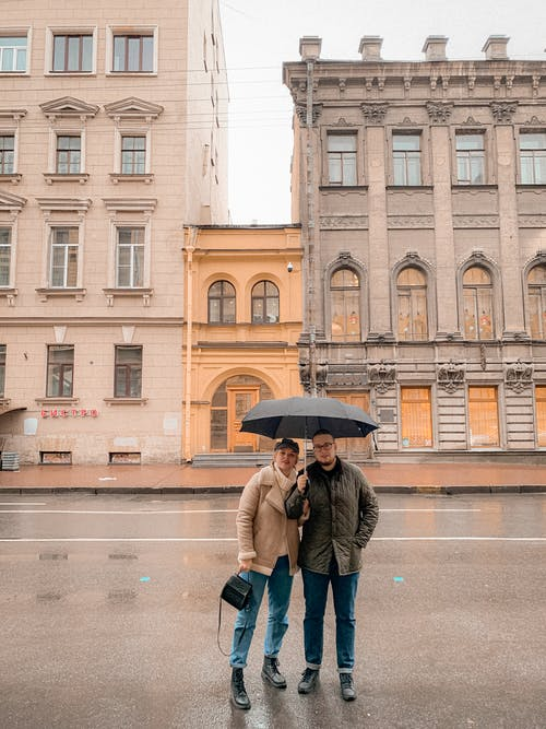 Full body of young stylish man and woman in warm clothes relaxing on street with umbrella near aged buildings during sightseeing tour in city on rainy day
