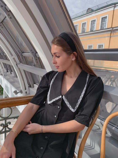 Dreamy young female resting on terrace of modern building