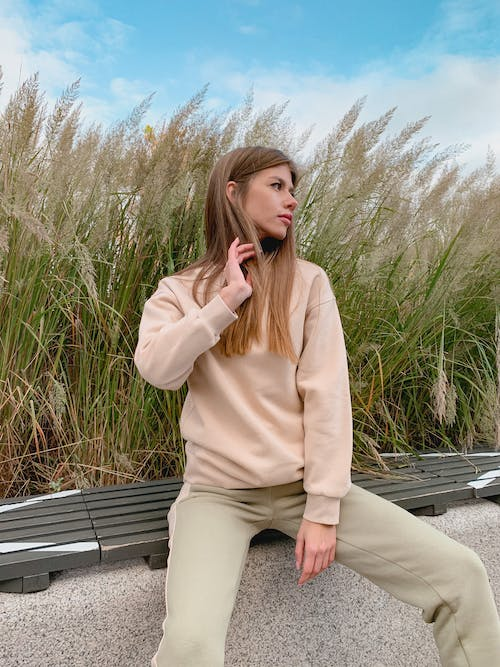 Confident young female in trendy outfit touching long hair and looking away while relaxing on bench in park on sunny day