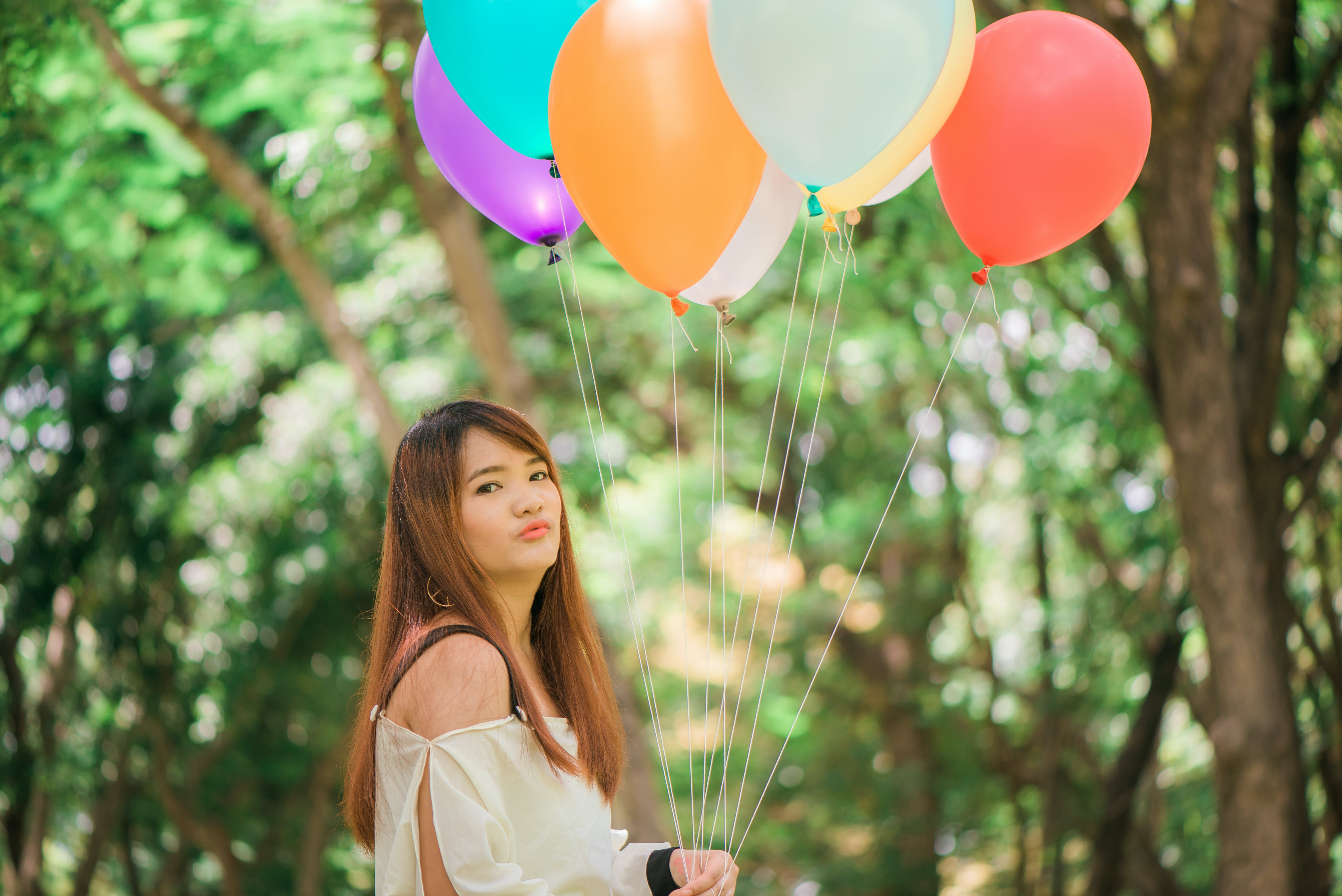 Woman Pouching Her Lips While Holding Balloons