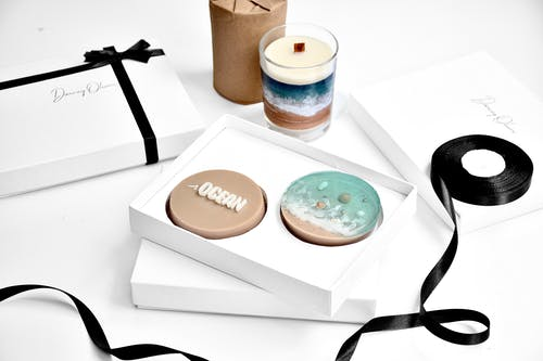 From above of bright round shaped soap with inscription in present box near candle in glass and rolled ribbon