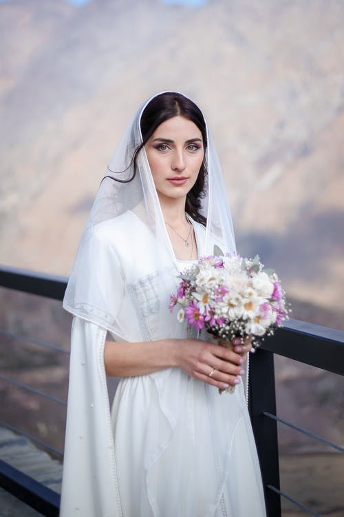 Young peaceful Georgian woman in traditional wedding dress and long veil holding bouquet looking at camera