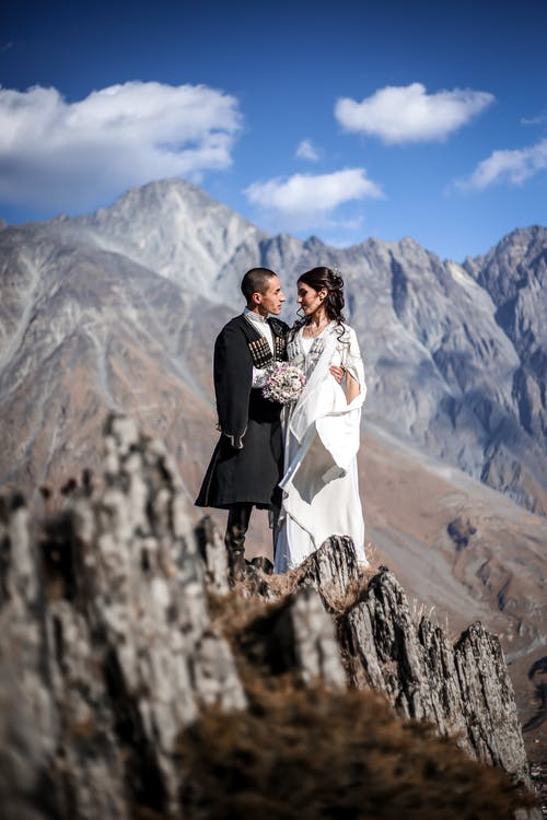 Loving ethnic couple in wedding suits on mountain rock