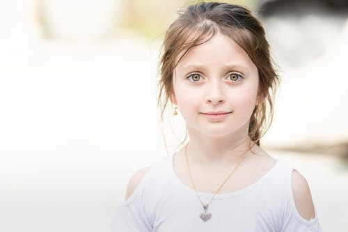 Positive little girl looking at camera on blurred background