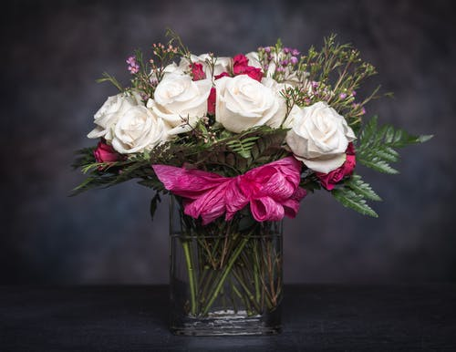 Elegant bouquet with fresh white and pink roses with fern leaves and wildflowers decorated with ribbon and placed in glass vase against black background