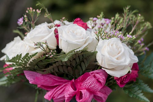 Tender bouquet of roses and small wildflowers in daylight