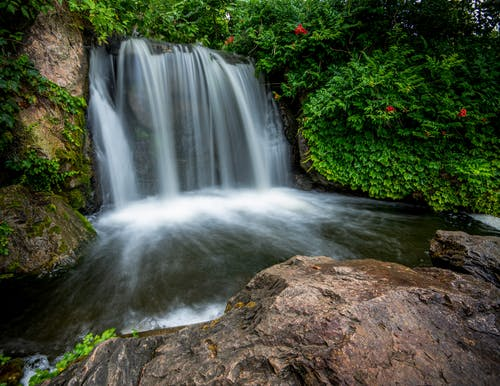 Picturesque view of cascade with rapid water flows in mounts with blooming flowers in summer