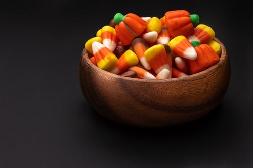 Round shaped wooden bowl with pile of assorted bright gummy candies with ribbed surface