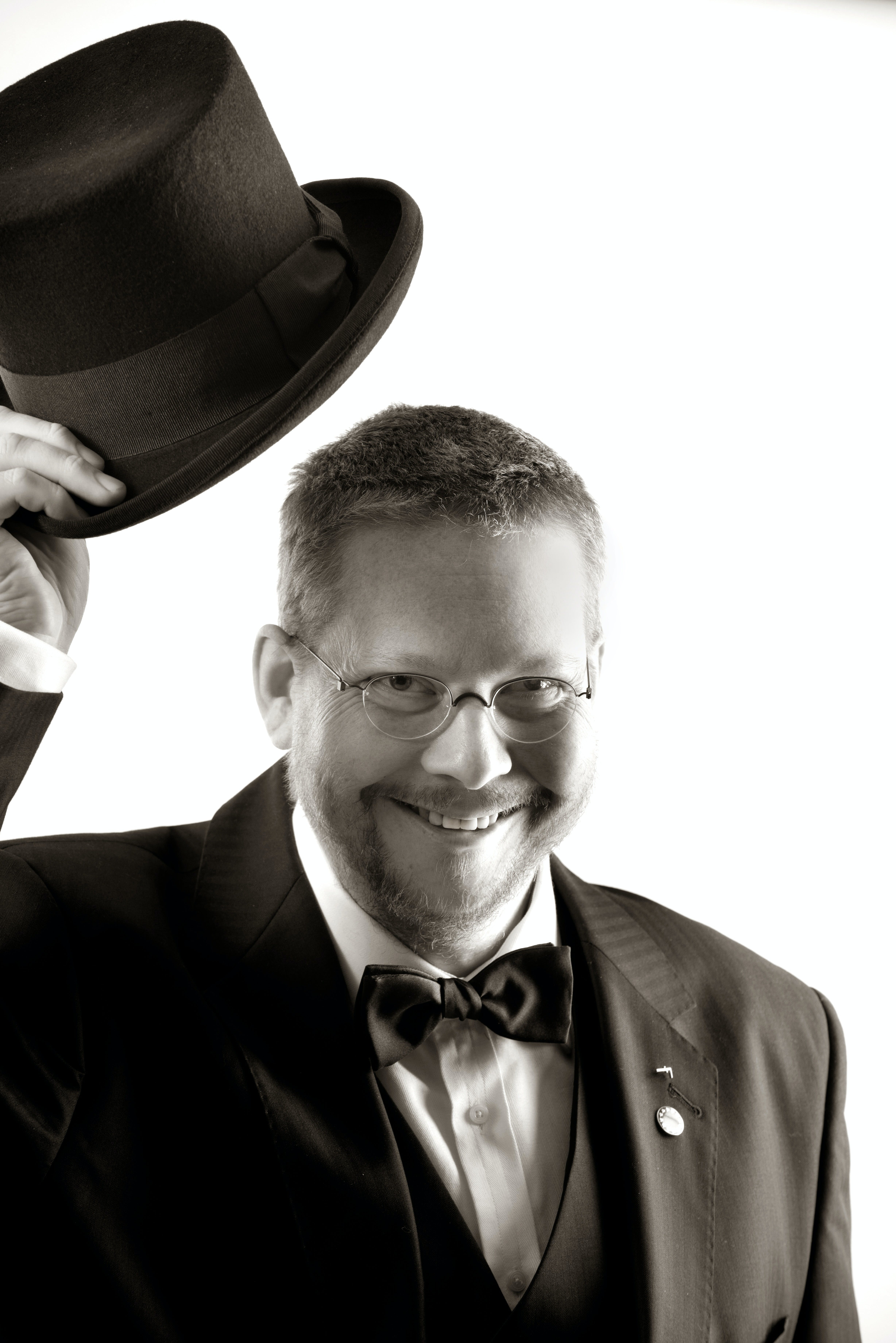 Man in Tuxedo and Eyeglasses Holding Top Hat in Grayscale